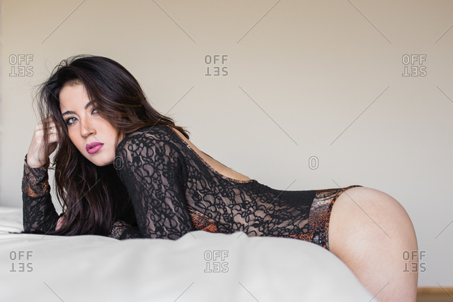 Side view of slim sexy female wearing black lace bodysuit lying on bed and looking at camera