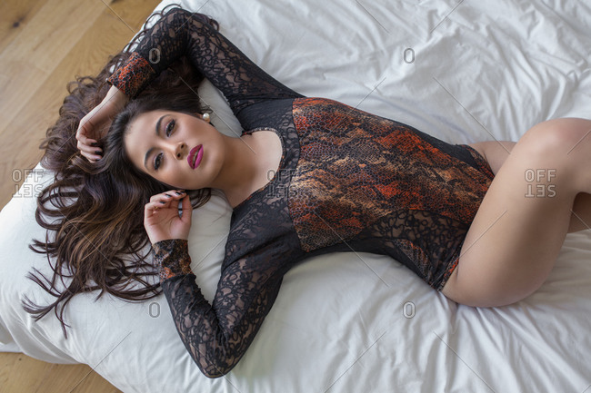 From above of slim sexy female wearing black lace bodysuit lying on bed and looking at camera