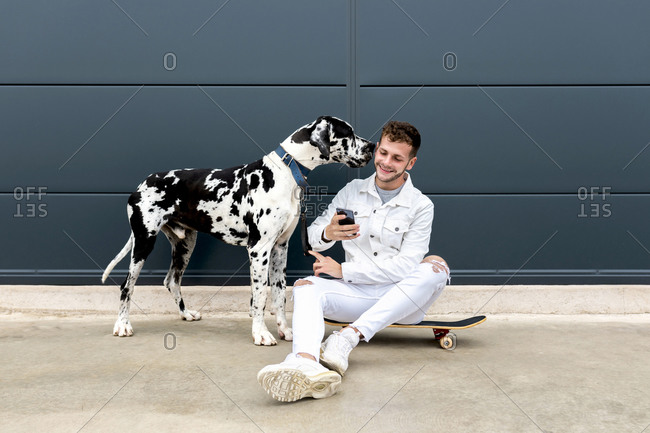 Cheerful young male cuddling Great Dane dog and taking self portrait on smartphone while sitting together in city
