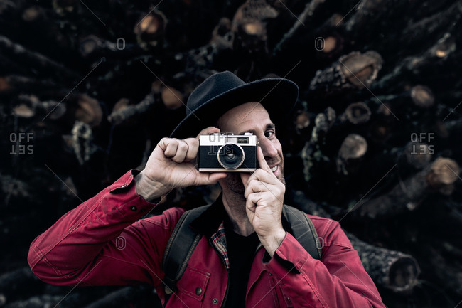 Content adult man in hat taking photo with vintage photo camera while standing at pile of lumber logs