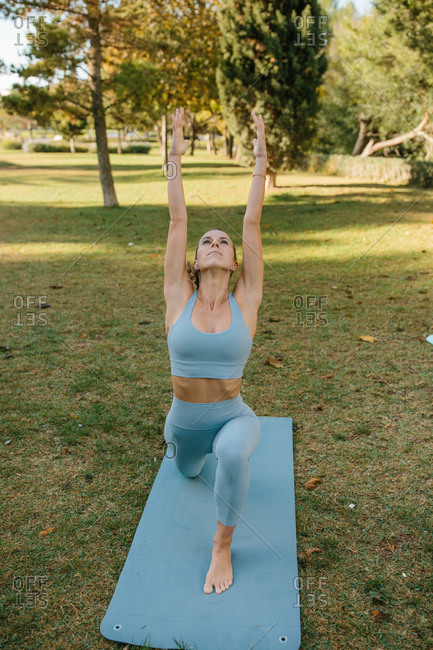 Full body of young slim barefoot female in blue sportswear standing in Crescent Lunge on the Knee pose while practicing yoga on green lawn in park