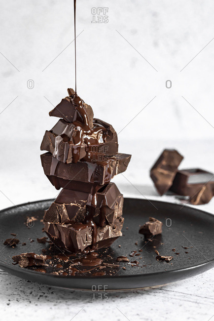 Pouring melted chocolate onto stack of chocolate cubes