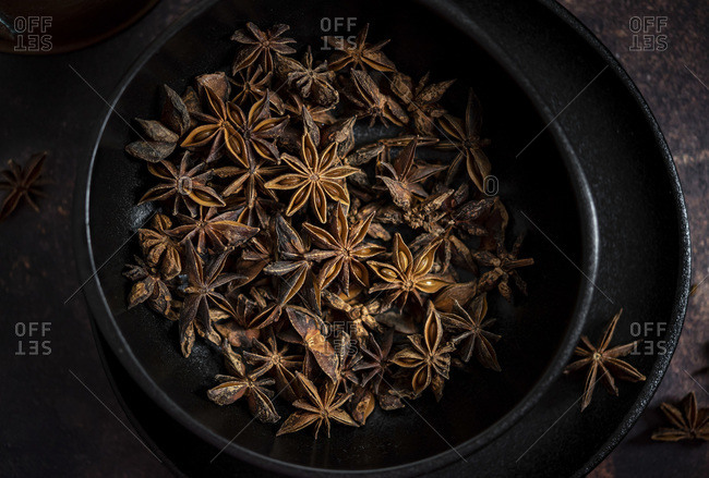 Star anise pods in a black plate