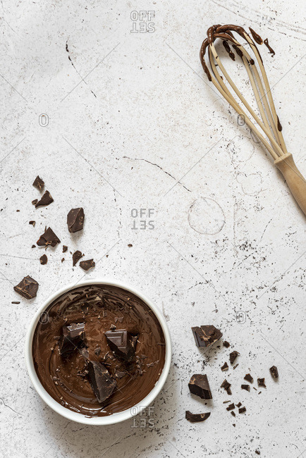 Bowl of melted chocolate with wooden whisk