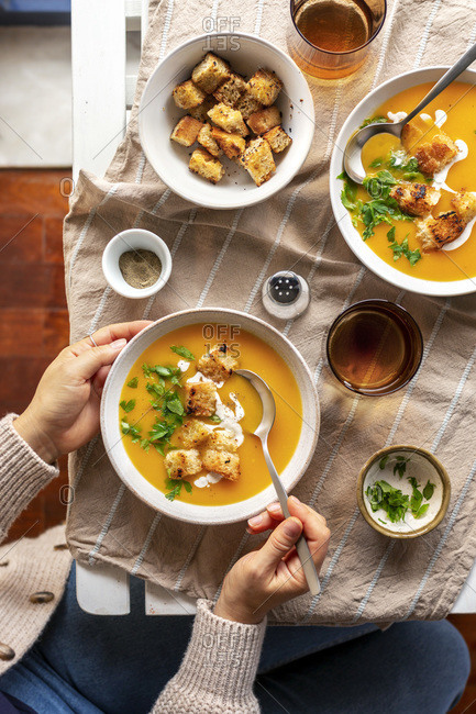Female eating butternut squash soup from a bowl.
