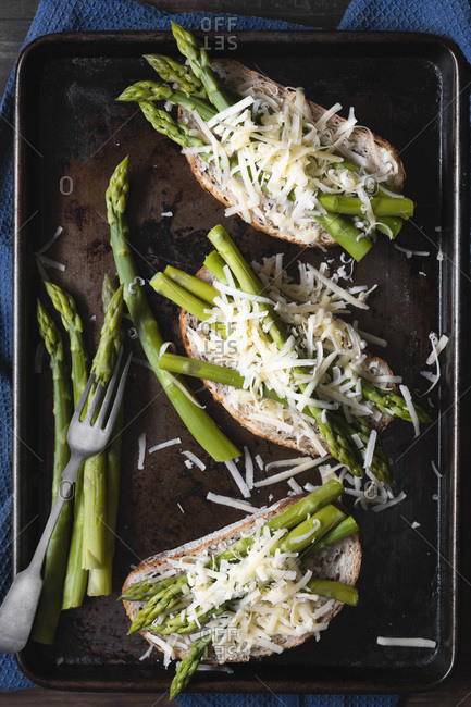 Preparation of  cheese and asparagus on sourdough bread.