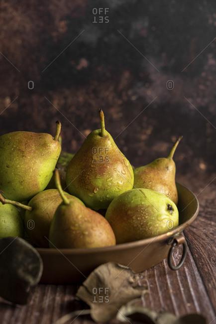 Fresh raw pears in a copper baking pan