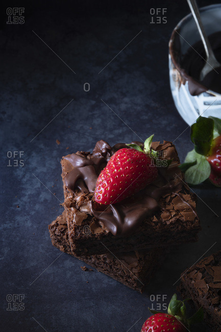 Decoration of brownies with melted chocolate and strawberries.