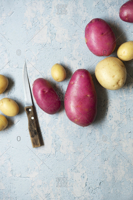 Red and white potatoes on a textured blue background.