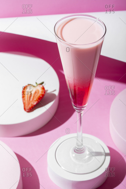 Pink cocktail on a pink background. Minimalistic set design.