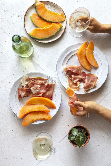 Flat-lay of prosciutto and cantaloupe with white wine