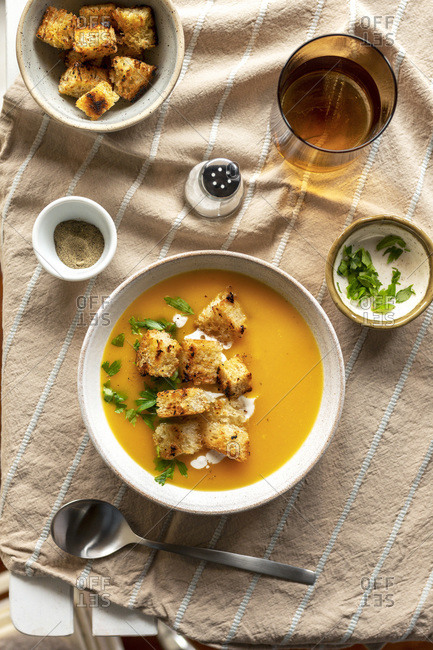 Butternut squash soup in a bowl with croutons and parsley