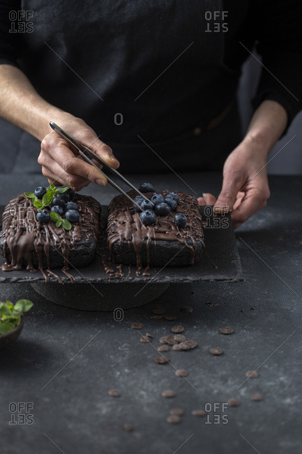 Pastry chef decorates brownie cake with blueberries and mint leaves.