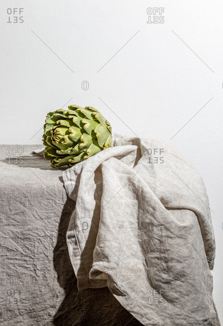 Artichoke on the table covered with a gray linen tablecloth