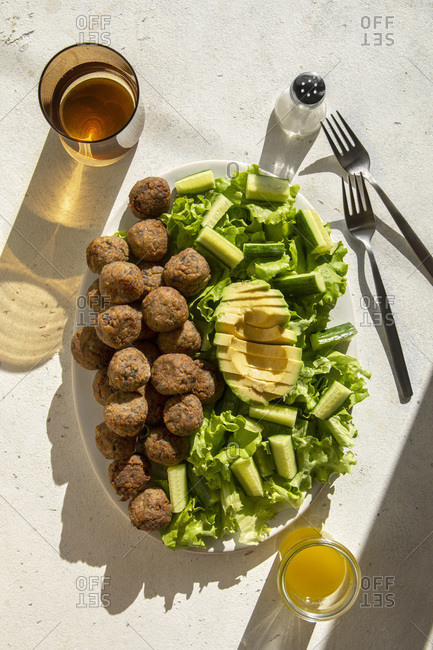 Vegetarian meatballs with lettuce, cucumber and avocado salad in a bowl