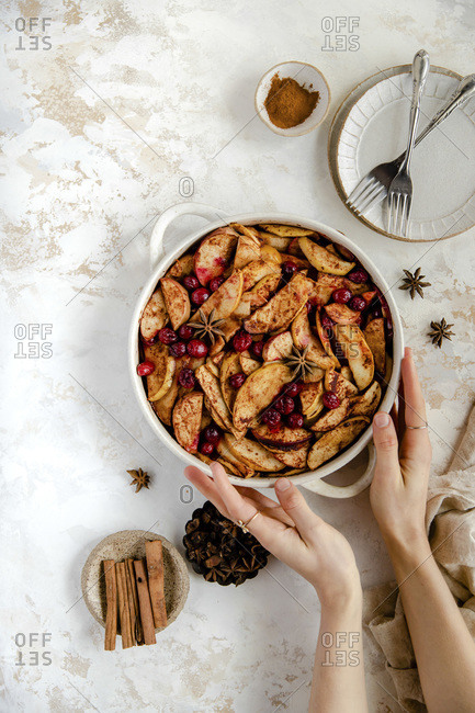 Baked apple and cranberry dessert with hands holding the dish.