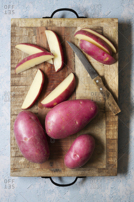 Whole and sliced red potatoes on a wooden cutting board.