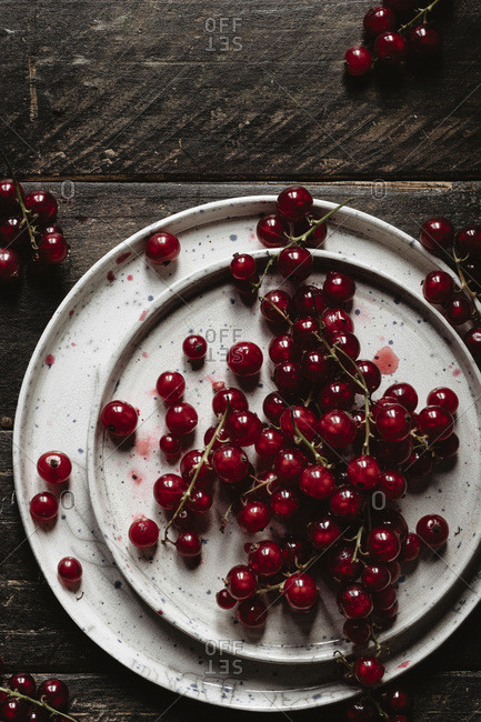 Red currants on a ceramic plate onto a wooden backdrop