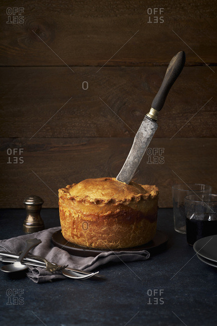 Cutting traditional British raised pork pie with bacon and herbs