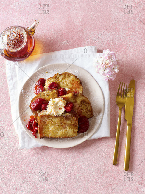 French toast breakfast casserole with poached strawberries and powdered sugar