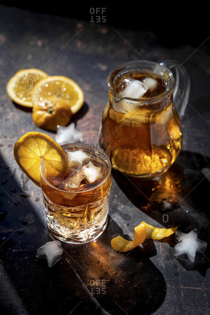 Glass of cold orange drink with ice cubes and orange slices