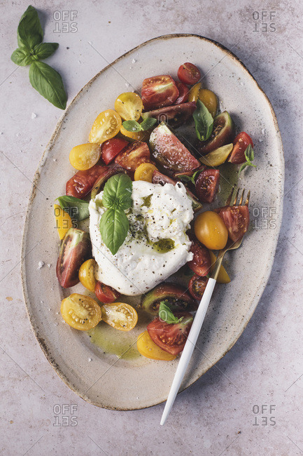 Heirloom tomato salad with burrata and olive oil on light background.