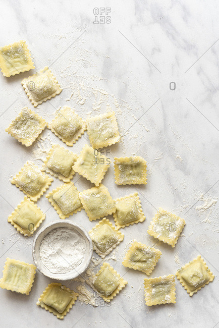 Homemade Ravioli and a little bowl of flour on a marble surface