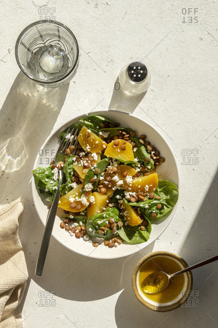Golden beet salad with green lentil, feta cheese and spinach in a bowl