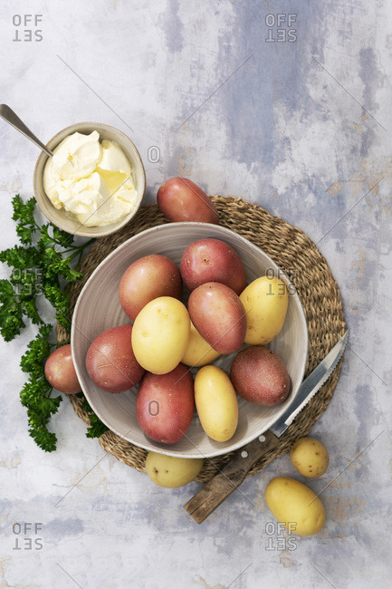 Red and white potatoes in a ceramic bowl, parsley and sour cream.