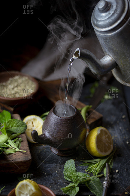 Latin American hot drink yerba mate in clay cup, herbs and lemon.