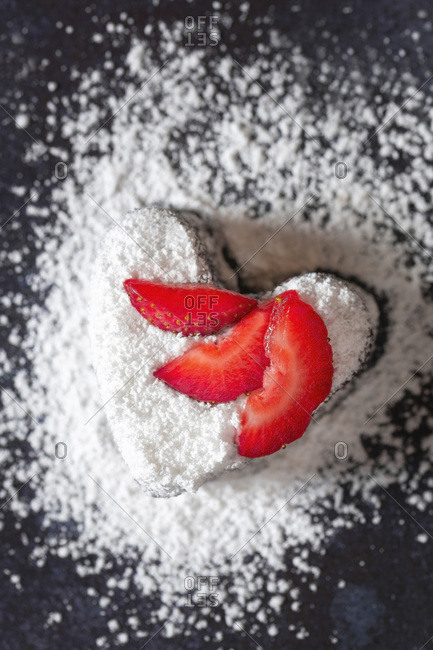 Heart shaped brownie dusted with icing sugar and decorated with slices of strawberry.