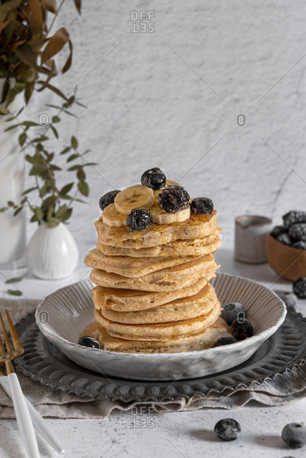 Stack of dairy free whole wheat pancakes served with honey, banana and berries