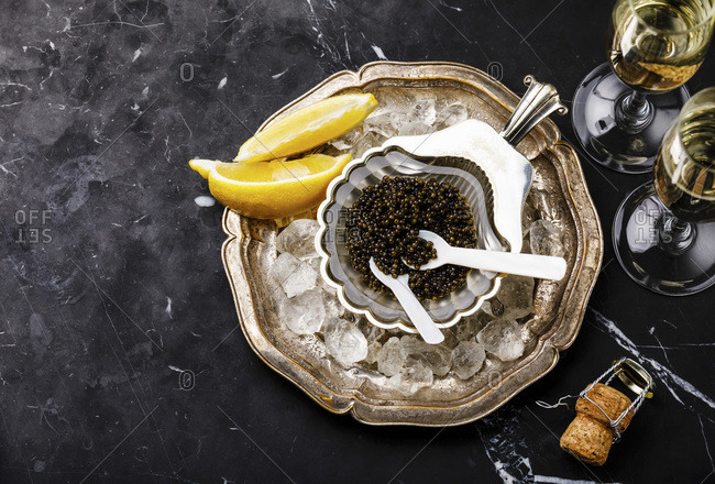 Black caviar in silver bowl and Champagne on black marble background copy space