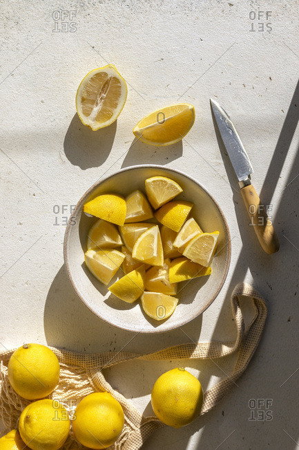 Sliced lemon in a bowl and a reusable string shopping bag on the table