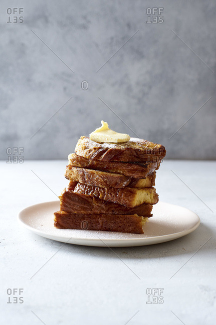 A pile of French toasts for breakfast with butter and powdered sugar side view