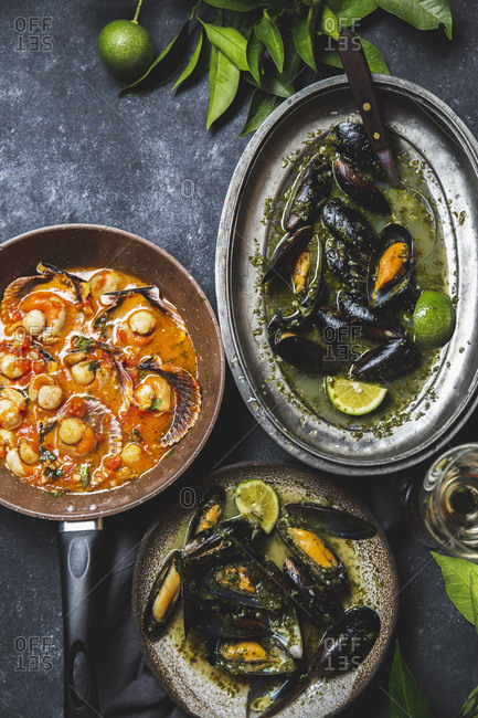 Mussels in green herb and white wine sauce and scallops in tomato white wine sauce.