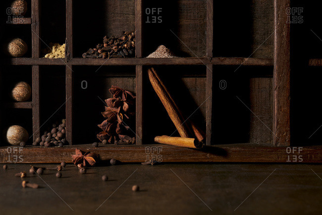 Warm, fall spices arranged in a rustic wooden tray. Warm, brown tones with moody lighting.