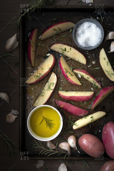 Potato wedges coated with olive oil and seasoned with rosemary and salt on a baking tray.