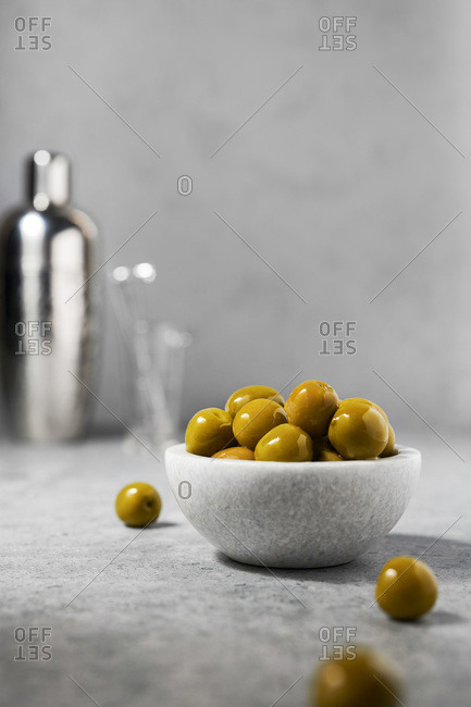 Marble bowl full of green olives with martini shaker in the background. Gray surface and background.