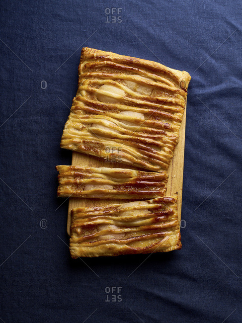 Dartois with pears - French puff pastry tart with fruits and frangipane on dark blue background