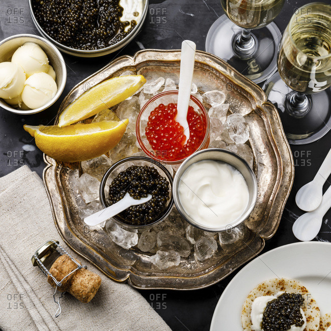 Red and Black Caviar, Mini Pancakes and Sour Cream Holiday Party Appetizer on dark marble background