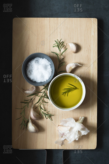 Bowls of salt flakes and olive oil with rosemary and garlic cloves on a wooden cutting board.