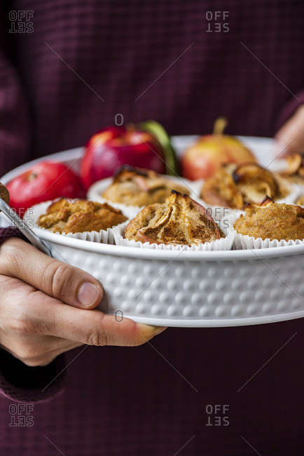 Woman with a claret red sweater holding a white pan full of apple cinnamon muffins and apples.