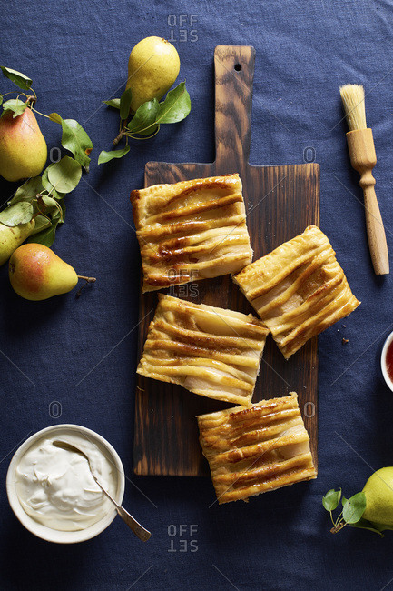 Sliced dartois with pears - French puff pastry tart with fruits and frangipane on dark blue background