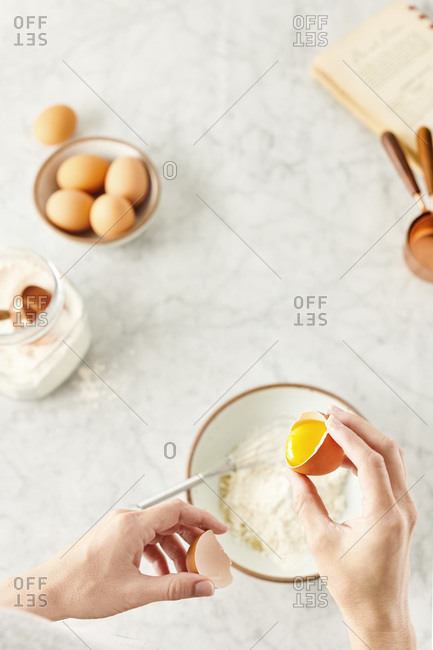 Baking ingredients on a marble surface with a woman cracking an egg over a mixing bowl of flour.