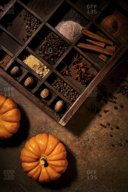 Warm, fall spices arranged in a rustic wooden tray with orange pumpkins.  Warm, brown tones with moody lighting.