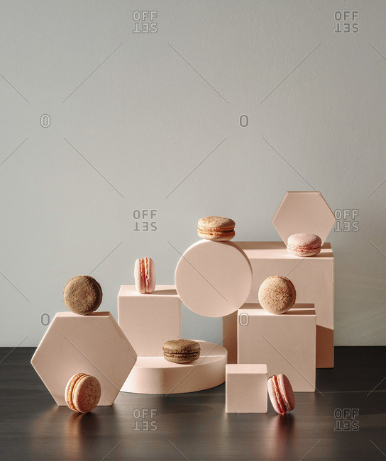 Creative shot of French macarons with geometrical shapes compositions. Modern trendy still life in pastel colors. Copy space