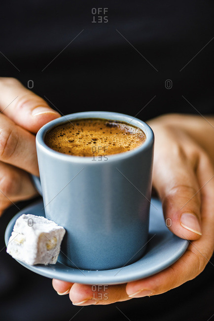 Woman with a black sweater holding Turkish coffee in a grey coffee cup, a Turkish delight on the side.