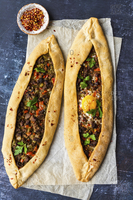 Turkish pide stuffed with beef and an egg photographed on a piece of baking paper on a dark background.