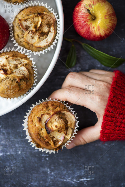 Woman with a red sweater holding an apple cinnamon muffin, other muffins and apples accompany on a dark background.